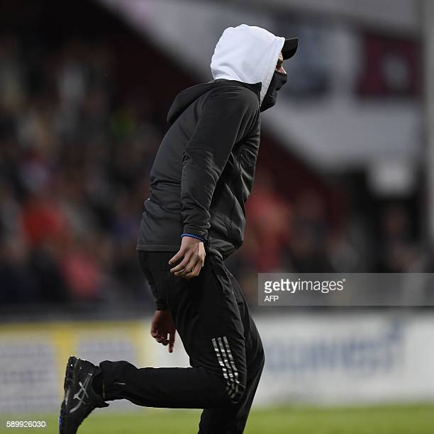A masked soccer spectator runs on the pitch during a football match between Jonkoping Sodra and Ostersund in Jonkoping on August 15 2016 / AFP / TT...
