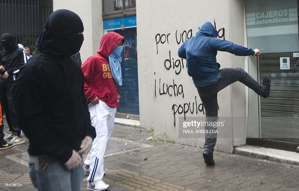 A masked student vandalizes a cash dispenser during a protest in Medellin, Antioquia department, Colombia on March 21, 2013, demanding a better and free education and an alternative university reform . AFP PHOTO/Raul ARBOLEDA