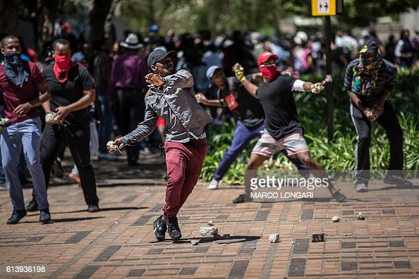 TOPSHOT Masked students from the Witwatersrand University engage in stone throwing with South Africa anti riot policemen in Johannesburg on October...