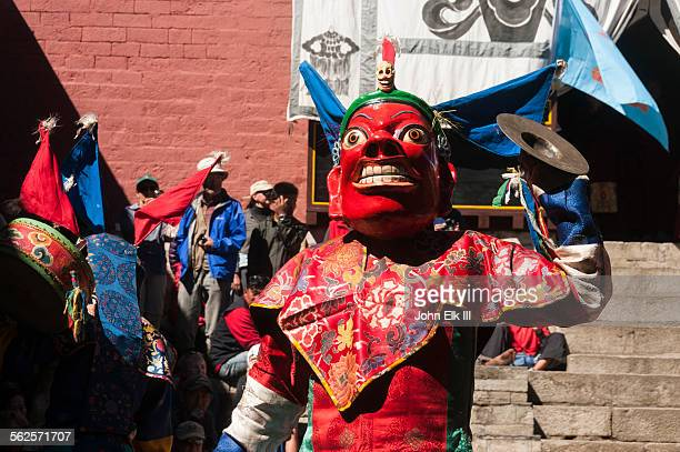 Masked temple dancer playing cymbals