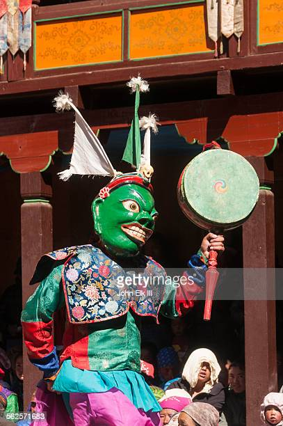 Masked temple dancer playing drum