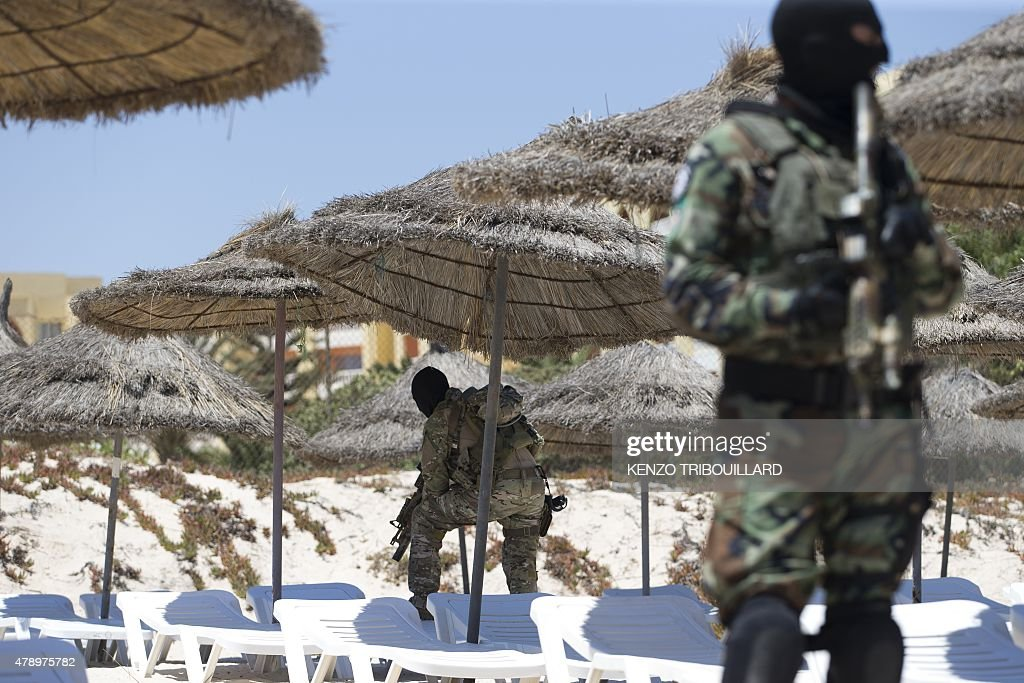 Masked Tunisian soldiers stand guard on the beach at the Riu Imperial Marhaba Hotel in Port el Kantaoui on the outskirts of Sousse south of the...