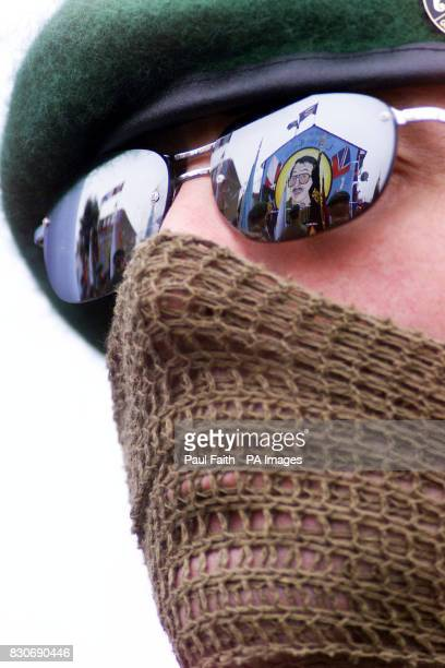 A masked UFF man pays his respects at a mural to the organisation's Jackie Coulter Coulter was shot dead in a Loyalist feud between the UVF and the...