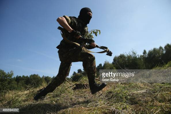 A masked Ukrainian soldier charges forward in an ambush on a Lithuanian convoy on the third day of the 'Rapid Trident' bilateral military exercises...