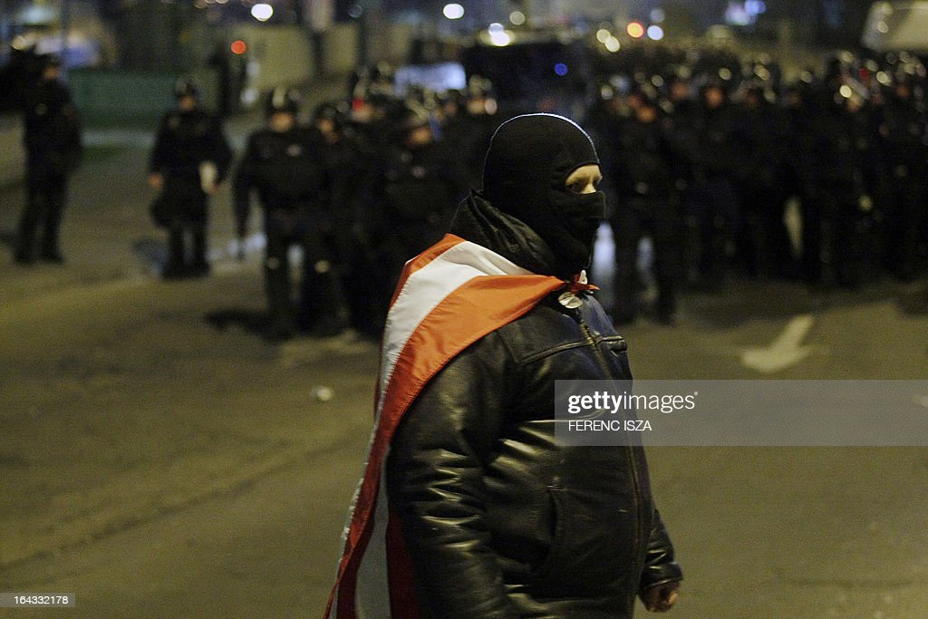 A masked Ultra Hungarian soccer fan faces with police officers during a clash between them and the police outside of the Puskas stadium after the Hungary vs Romania FIFA 2014 World Cup qualifying football match in Budapest, on March 22, 2013. FIFA ordered Hungary to play the 2014 World Cup qualifier match behind closed doors after fans hurled anti-Semitic abuse during a friendly match with Israel in August 2012.