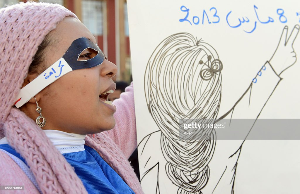 A masked woman shouts a slogan as Moroccan women demonstrate during the celebration of the International Women's Day on March 8, 2013, in Rabat. The International Women's Day is marked on March 8 every year.
