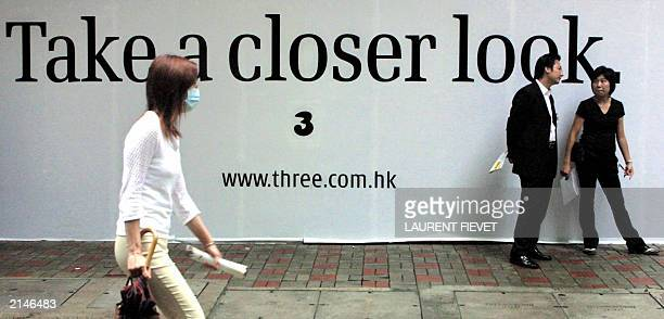 A masked woman walks past a soon to be opened Hutchison 3G shop as two property agents chat in Hong Kong 14 June 2003 Hutchison Wampoa's right to use...