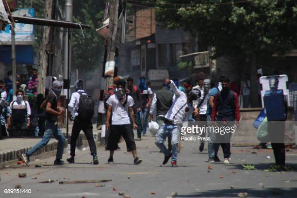 A masked youth throwing stone towards government forces in Srinagar May 27 2017 Civilian was killed and dozens of others injured in Indiancontrolled...