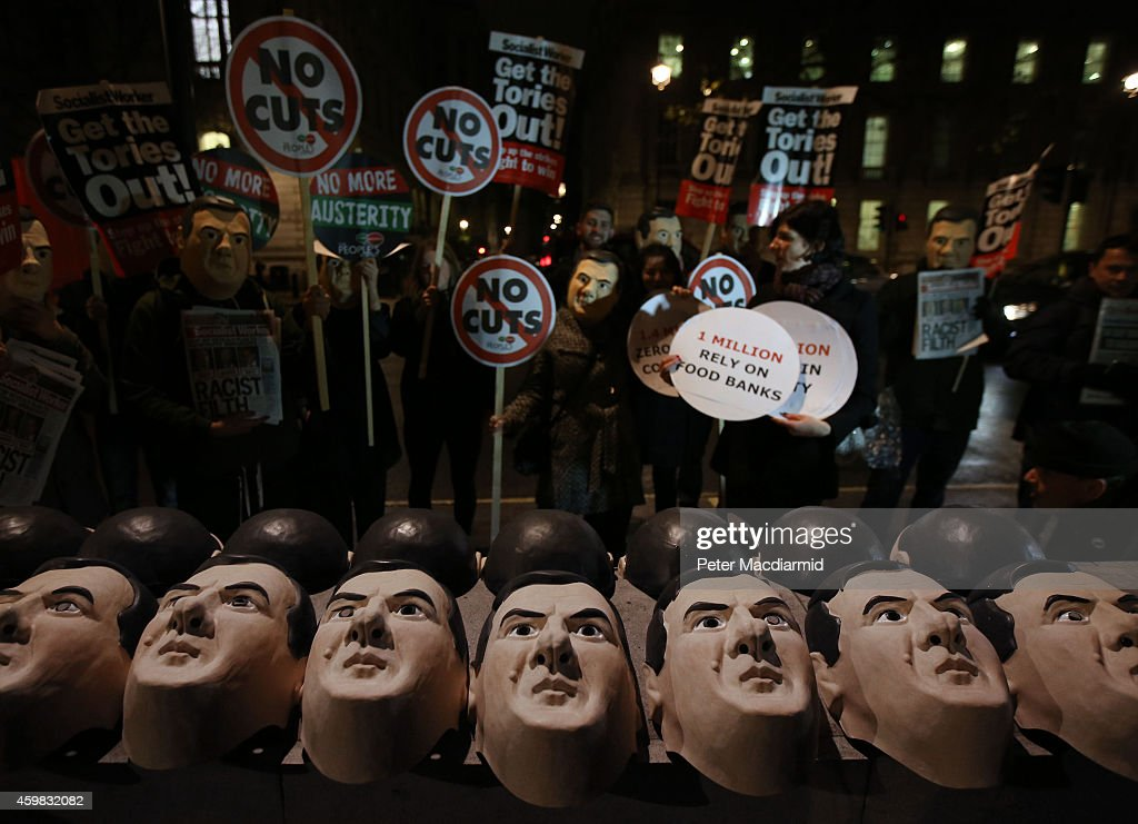 Masks depicting Chancellor of the Exchequer George Osborne are lined up on a wall opposite Downing Street by anti austerity protestors on December 2...