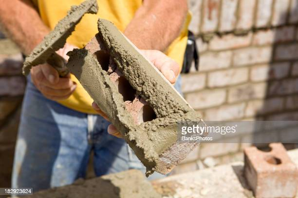 Mason Buttering a Brick with Mortar
