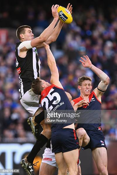 Mason Cox of the Magpies marks over the top of Tom McDonald of the Demons during the round 12 AFL match between the Melbourne Demons and the...