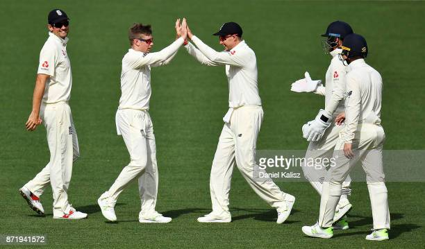 Mason Crane of England celebrates with Joe Root of England after taking a wicket during day two of the Four Day Tour match between the Cricket...