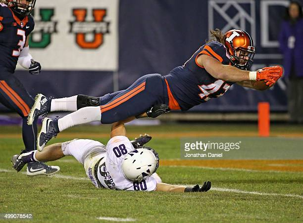 Mason Monheim of the Illinois Fighting Illini dives over Austin Carr of the Northwestern Wildcats to score a touchdown after intercepting a pass at...