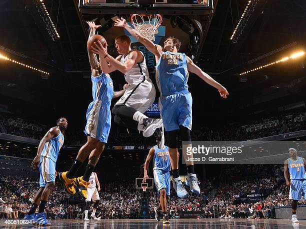 Mason Plumlee of the Brooklyn Nets looks to pass the ball in midair against the Denver Nuggets on December 23 2014 at the Barclays Center in Brooklyn...