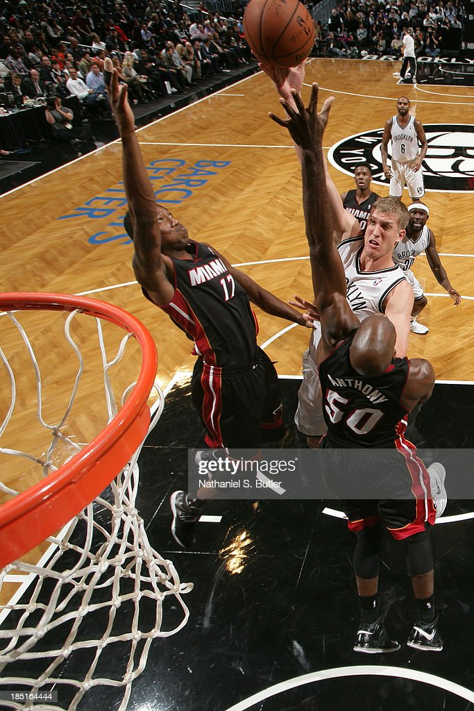 Mason Plumlee #1 of the Brooklyn Nets shoots against Eric Griffin #17 and Joel Anthony #50 of the Miami Heat during a preseason game at the Barclays Center on October 17, 2013 in the Brooklyn borough of New York City.