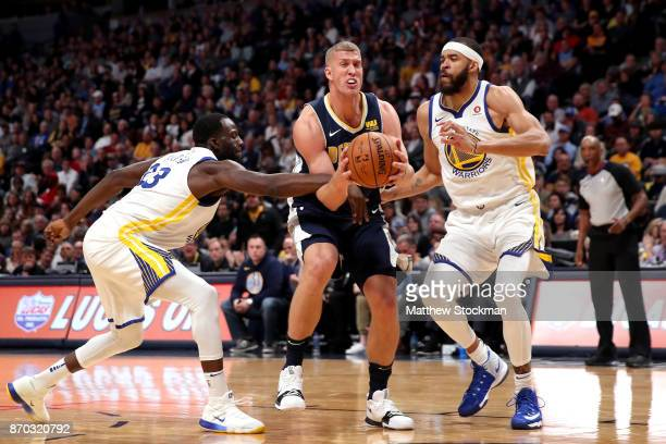 Mason Plumlee of the Denver Nuggets drives to the basket against Javale McGee of the Golden State Warriors and is fouled by Draymond Green at the...