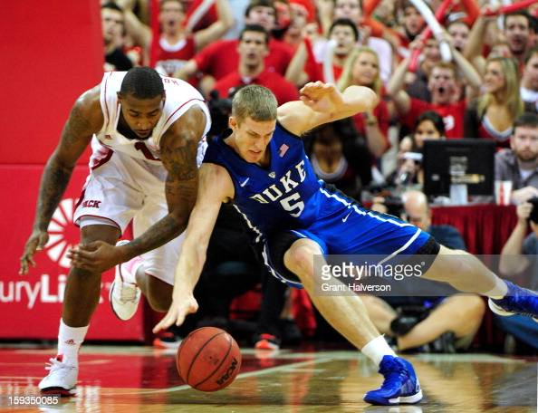 Mason Plumlee of the Duke Blue Devils battles for a loose ball with Richard Howell of the North Carolina State Wolfpack during play at PNC Arena on...