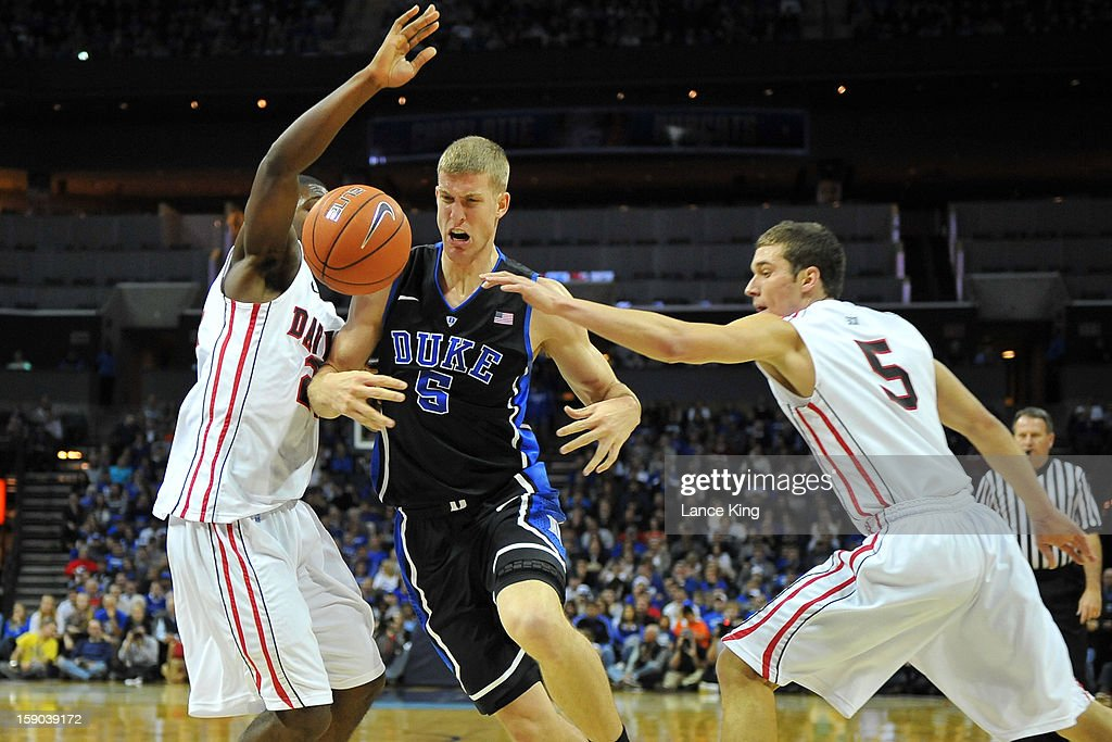 Mason Plumlee #5 of the Duke Blue Devils loses the ball while defended by De'Mon Brooks #24 and JP Kuhlman #5 of the Davidson Wildcats at Time Warner Cable Arena on January 2, 2013 in Charlotte, North Carolina. Duke defeated Davidson 67-50.