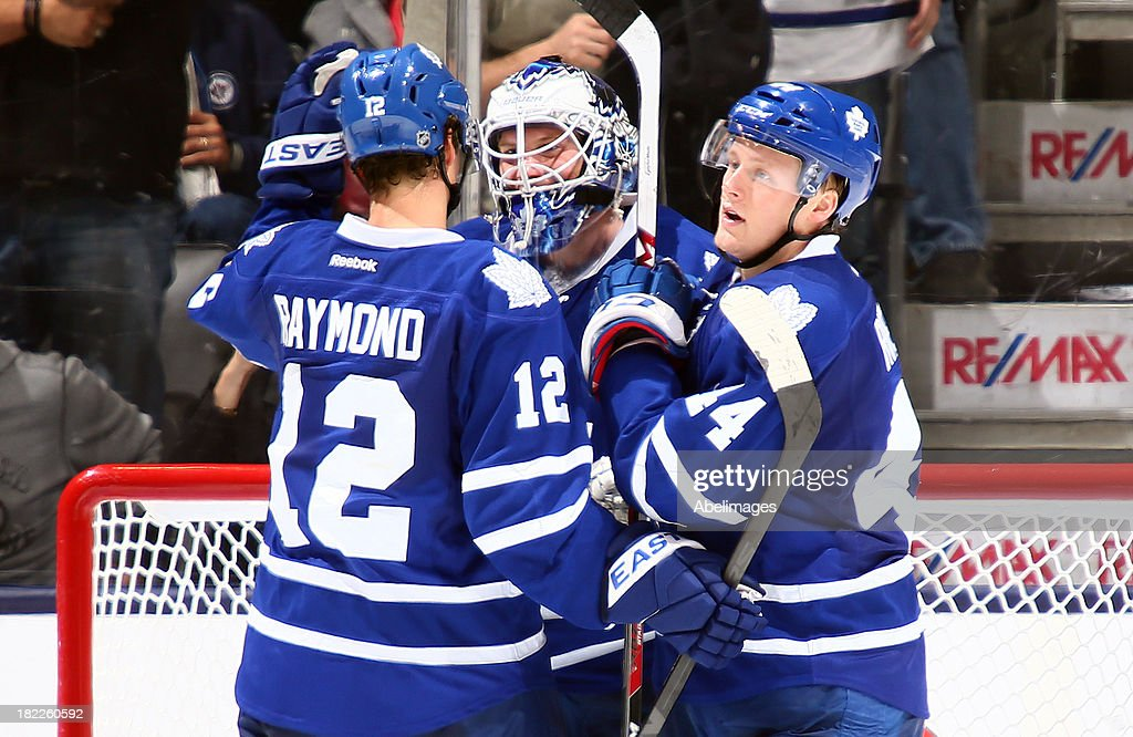 Mason Raymond #12, Morgan Rielly #44 and James Reimer #34 of the Toronto Maple Leafs celebrate a win against the Detroit Red Wings during NHL Preseason action at the Air Canada Centre September 28, 2013 in Toronto, Ontario, Canada.
