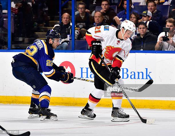 Mason Raymond of the Calgary Flames controls the puck as Kevin Shattenkirk of the St Louis Blues defends on October 11 2014 at Scottrade Center in St...