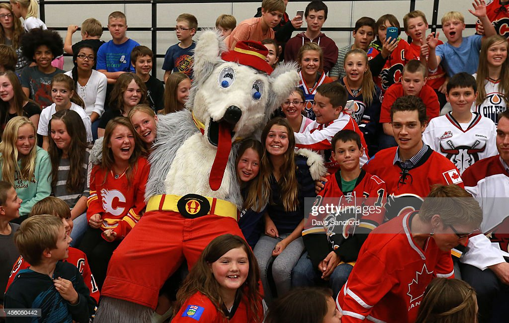 Mason Raymond of the Calgary Flames Jordan Szwarz of the Arizona Coyotes and Calgary Flames Mascot Harvey the Hound pose for a group shot with...