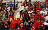 Mason Raymond of the Calgary Flames Jordan Szwarz of the Arizona Coyotes and Calgary Flames Mascot Harvey the Hound pose for a group shot with...