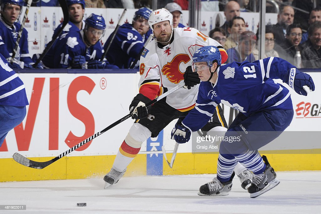 Mason Raymond #12 of the Toronto Maple Leafs defends as Brian McGrattan #16 of the Calgary Flames passes the puck during NHL game action April 1, 2014 at the Air Canada Centre in Toronto, Ontario, Canada.
