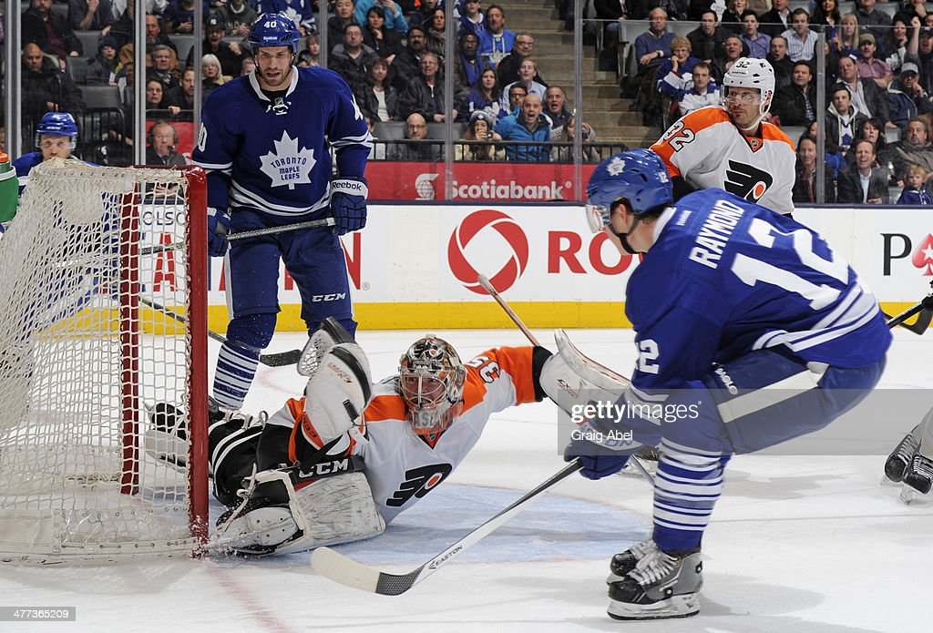 <a gi-track='captionPersonalityLinkClicked' href=/galleries/search?phrase=Mason+Raymond&family=editorial&specificpeople=4521385 ng-click='$event.stopPropagation()'>Mason Raymond</a> #12 of the Toronto Maple Leafs scores a third period goal on Steve Mason #35 of the Philadelphia Flyers during NHL game action March 8, 2014 at the Air Canada Centre in Toronto, Ontario, Canada.