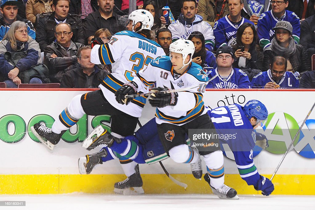Mason Raymond #21 of the Vancouver Canucks falles to the ice after colliding with Adam Burish #37 of the San Jose Sharks during an NHL game at Rogers Arena on March 5, 2013 in Vancouver, British Columbia, Canada.
