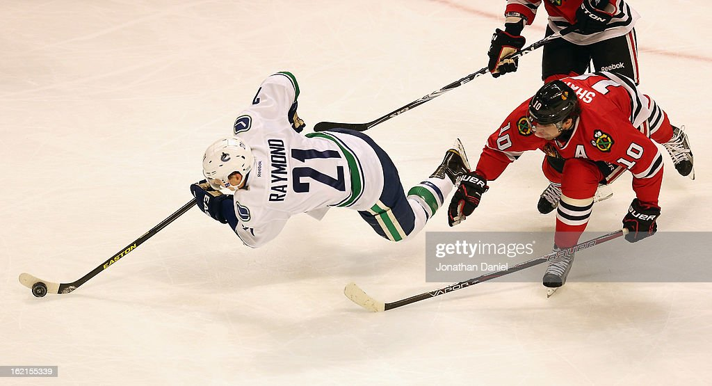 <a gi-track='captionPersonalityLinkClicked' href=/galleries/search?phrase=Mason+Raymond&family=editorial&specificpeople=4521385 ng-click='$event.stopPropagation()'>Mason Raymond</a> #21 of the Vancouver Canucks looses his balance as he tries to advance the puck in front of <a gi-track='captionPersonalityLinkClicked' href=/galleries/search?phrase=Patrick+Sharp&family=editorial&specificpeople=206279 ng-click='$event.stopPropagation()'>Patrick Sharp</a> #10 of the Chicago Blackhawks at the United Center on February 19, 2013 in Chicago, Illinois.