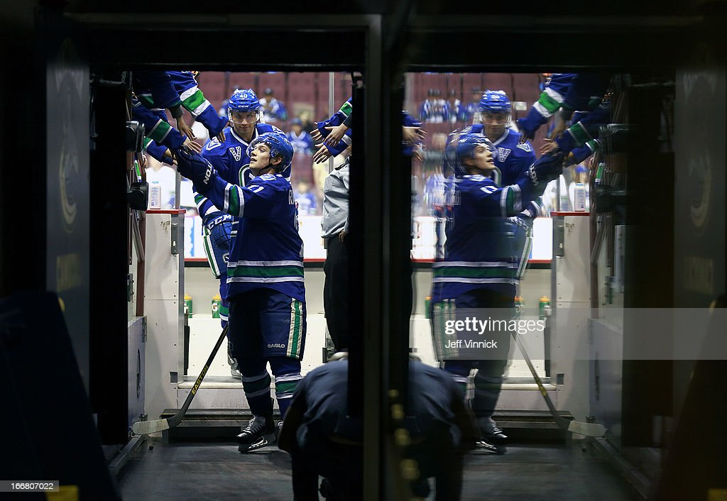 Mason Raymond #21 of the Vancouver Canucks passes a puck to a fan during their NHL game against the Phoenix Coyotes at Rogers Arena April 8, 2013 in Vancouver, British Columbia, Canada. Vancouver won 2-0.