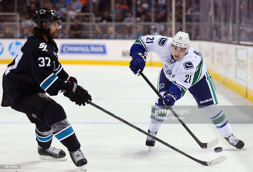 <a gi-track='captionPersonalityLinkClicked' href=/galleries/search?phrase=Mason+Raymond&family=editorial&specificpeople=4521385 ng-click='$event.stopPropagation()'>Mason Raymond</a> #21 of the Vancouver Canucks shoots the puck past <a gi-track='captionPersonalityLinkClicked' href=/galleries/search?phrase=Adam+Burish&family=editorial&specificpeople=696936 ng-click='$event.stopPropagation()'>Adam Burish</a> #37 of the San Jose Sharks in Game Three of the Western Conference Quarterfinals during the 2013 NHL Stanley Cup Playoffs at HP Pavilion on May 5, 2013 in San Jose, California. The Sharks defeated the Canucks 5-2.