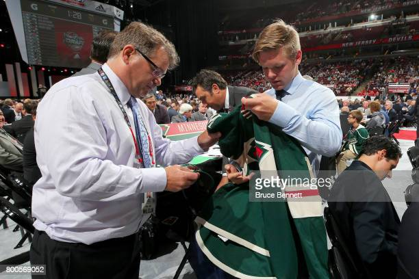 Mason Shaw puts on the Minnesota Wild jersey after being selected 97th overall during the 2017 NHL Draft at the United Center on June 24 2017 in...