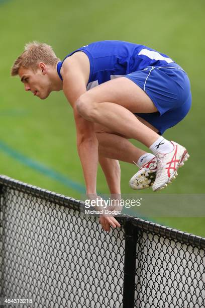 Mason Wood hops over the fence to retrieve a ball during a North Melbourne Kangaroos AFL training session at Arden Street Ground on August 29 2014 in...
