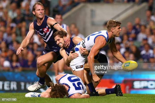 Mason Wood of the Kangaroos looks to pass the ball while being tackled by Joel Hamling of the Dockersduring the round five AFL match between the...