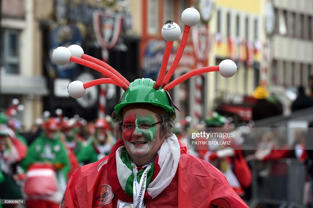 Masqueraded revellers celebrate the carnival sunday during the carnival season, on February 7, 2016 in Cologne, western Germany. Germany's carnival season is underway with increased security in Cologne, a city rocked by a rash of reported sexual assaults blamed on migrants. / AFP / PATRIK STOLLARZ