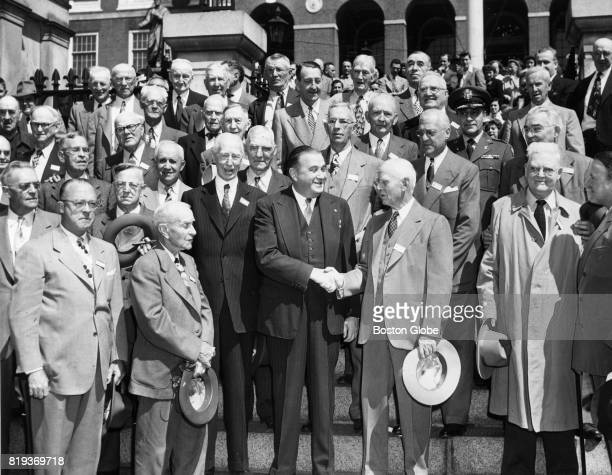 Mass Gov Paul Dever left shakes hands with Clark Griffith right as he greets oldtime favorite baseball players on the steps of the State House in...