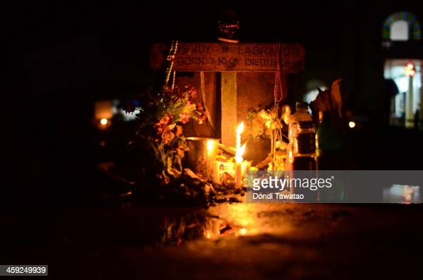 TACLOBAN LEYTE PHILIPPINES DECEMBER 24 A mass grave is lit by candles on Christmas eve on December 24 2013 in Palo Leyte Philippines Haiyan has been...