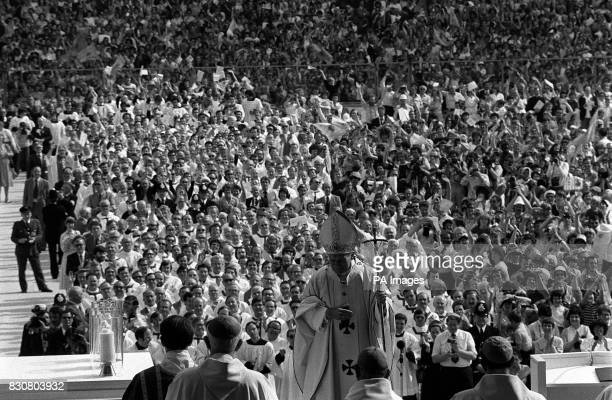 A mass of eager faces provide the backdrop as Pope John Paul II celebrates Mass before more than 70000 people at Wembley Stadium