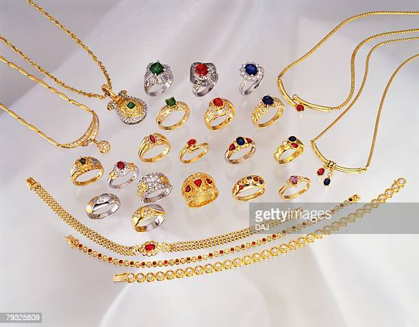 Mass of rings, necklaces and bracelets with jewels, high angle view, white background