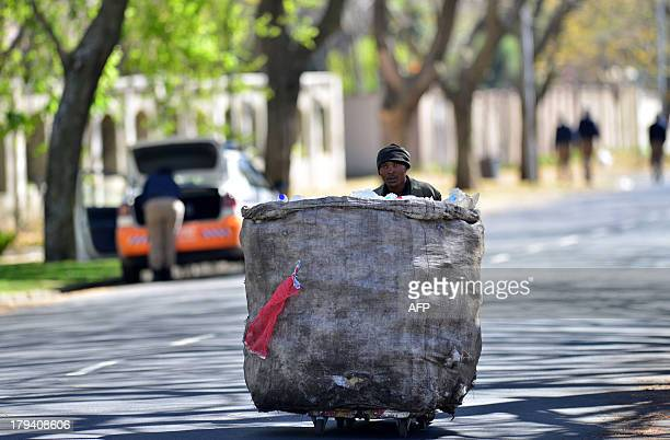 A mass pushes a bag of recyclable goods on September 3 2013 outside South Africa's antiapartheid icon Nelson Mandela's home in the Houghton area of...