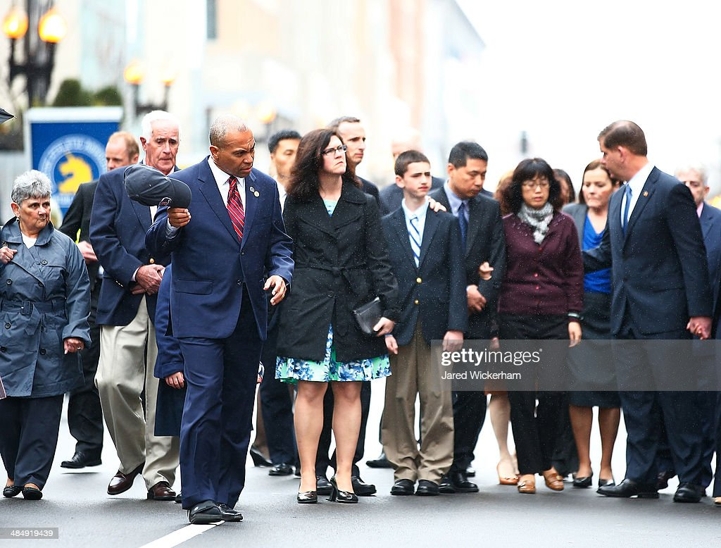 Massachusetts Governor Deval Patrick removes his hat during a wreathlaying ceremony with members of the victims families commemorating the oneyear...