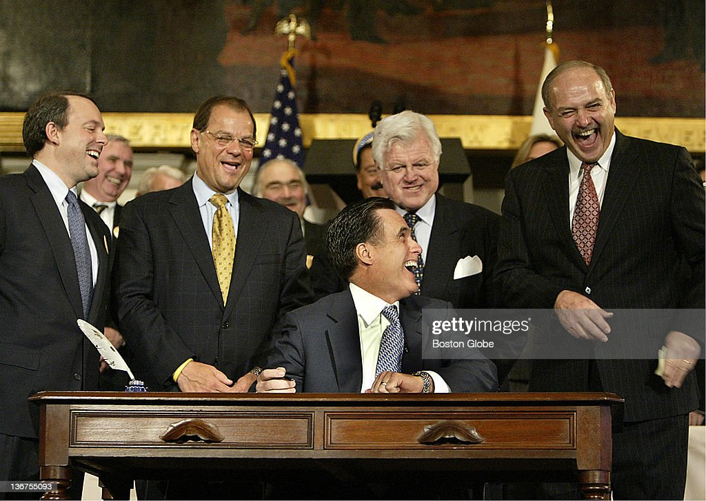 Massachusetts Governor Mitt Romney shares a laugh with House Speaker Salvatore DiMasi and other Democrats as the Republican signs the state's universal health care law at Faneuil Hall on April 12, 2006. Front row, left to right are Timothy Murphy, Massachusetts Health & Human Services Secretary, Robert E. Travaglini, Senate President, Sen. Edward M Kennedy and Salvatore DiMasi, Speaker of Mass. State House of Representatives.