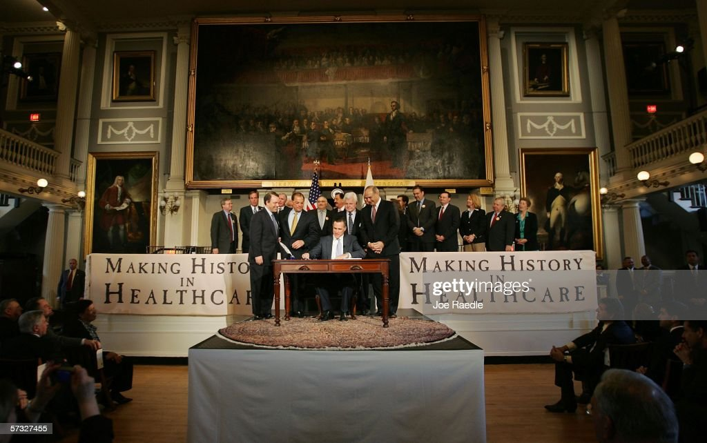 Massachusetts Governor Mitt Romney (seated) signs into law a new health care reform bill during a ceremony at Faneuil Hall April 12, 2006 in Boston, Massachusetts. U.S. Sen. Edward Kennedy (D-MA) (2nd R behind table) and others joined Romney for the signing of the bill, which makes Massachusetts the first state in the country to require that all residents have health insurance.