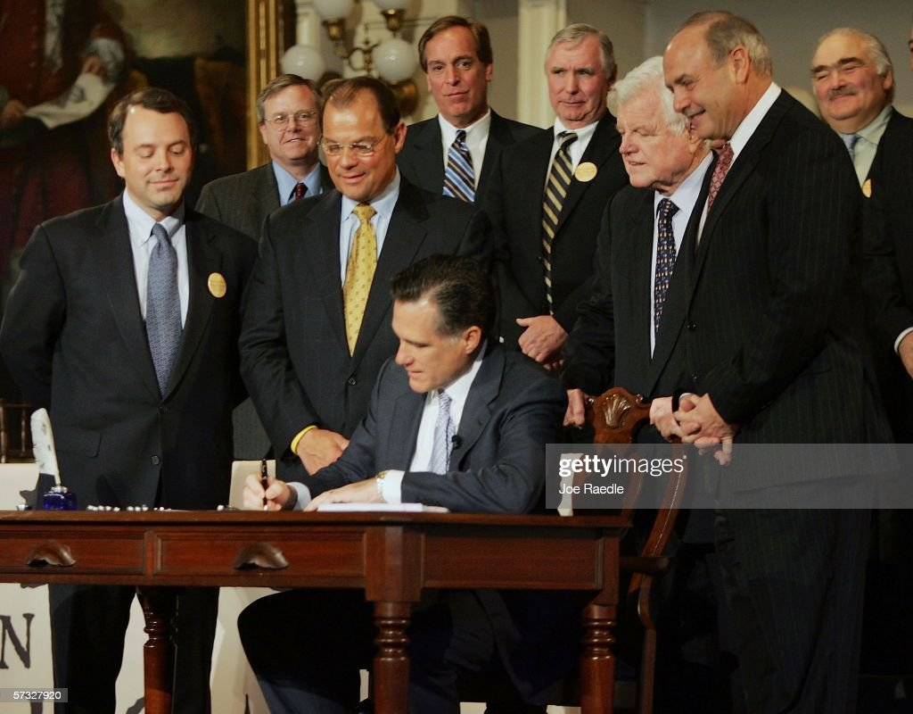 Massachusetts Governor Mitt Romney signs into law a new health care reform bill during a ceremony at Faneuil Hall April 12, 2006 in Boston, Massachusetts. U.S. Sen. Edward Kennedy (D-MA) (2nd R) and others joined Romney for the signing of the bill, which makes Massachusetts the first state in the country to require that all residents have health insurance.