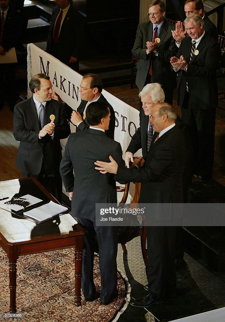 Massachusetts Governor Mitt Romney (back to camera) talks to U.S. Senator Edward Kennedy (D-MA) (L) and Mass. House Speaker Salvatore Dimasi after signing into law a new health care reform bill during a ceremony at Faneuil Hall April 12, 2006 in Boston, Massachusetts. The law makes Massachusetts the first state in the country to require that all residents have health insurance.
