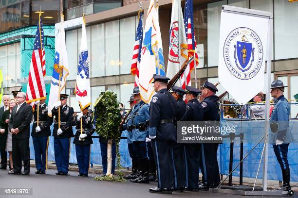 Massachusetts state and local police and fire department members present flags during a wreathlaying ceremony commemorating the oneyear anniversary...