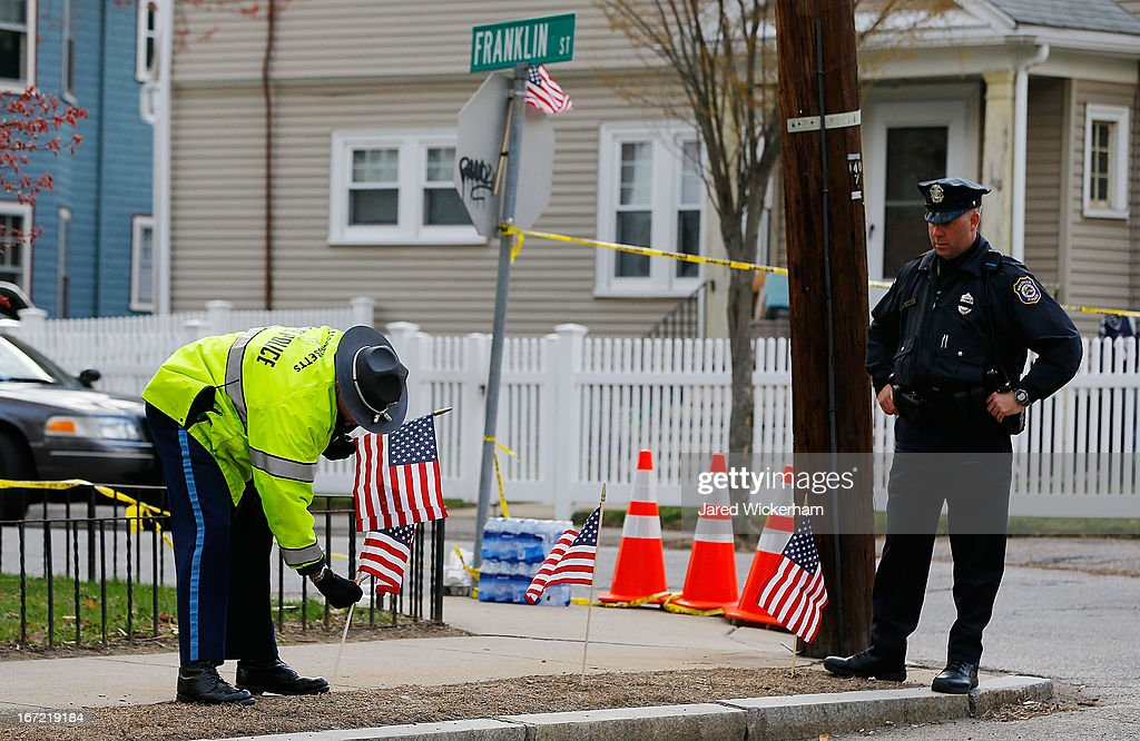 Massachusetts State Police officer and a Waltham Police officer set up American flags at the end of Franklin Street while many different members of...