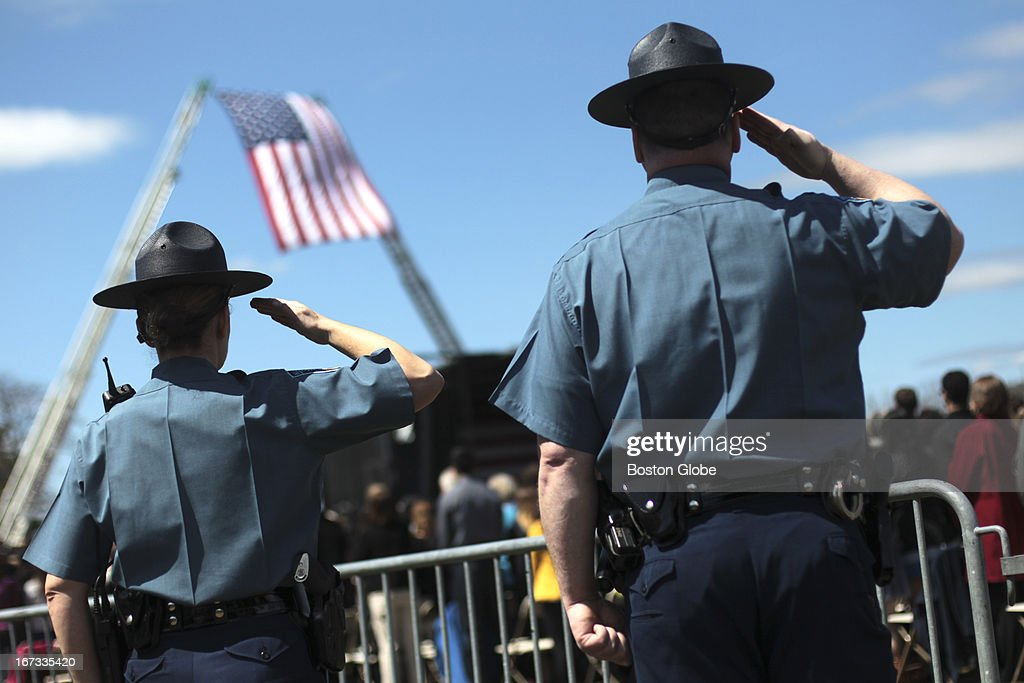 Massachusetts State Police salute during the memorial service for MIT police officer Sean Collier, at Briggs Field, on the MIT campus. Collier was killed during a shootout with the Boston Marathon bombing suspects.