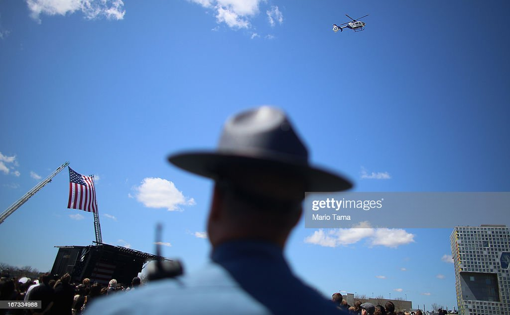 Massachusetts State Police trooper watches a ceremonial flyover at the memorial service for slain Massachusetts Institute of Technology police...